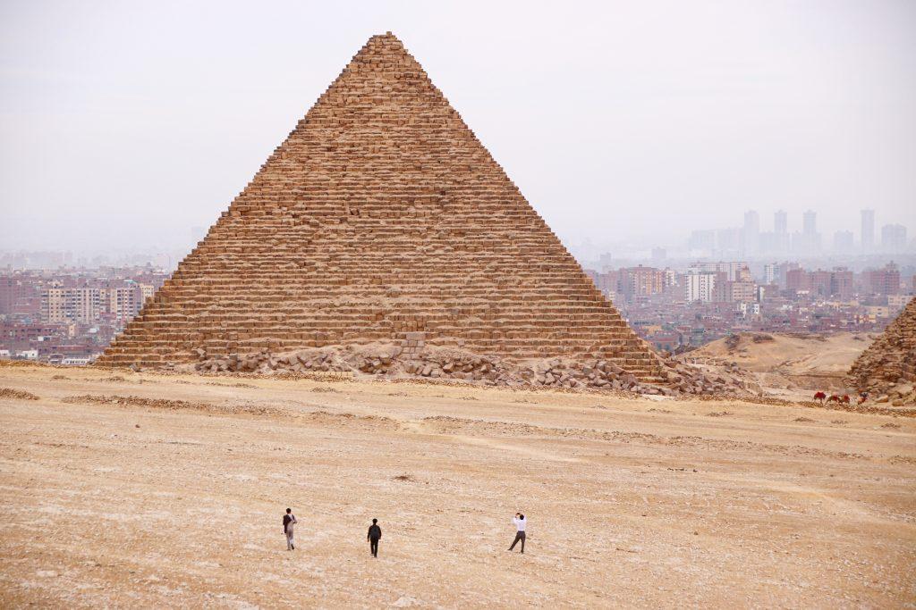 three men walking near pyramids of Egypt