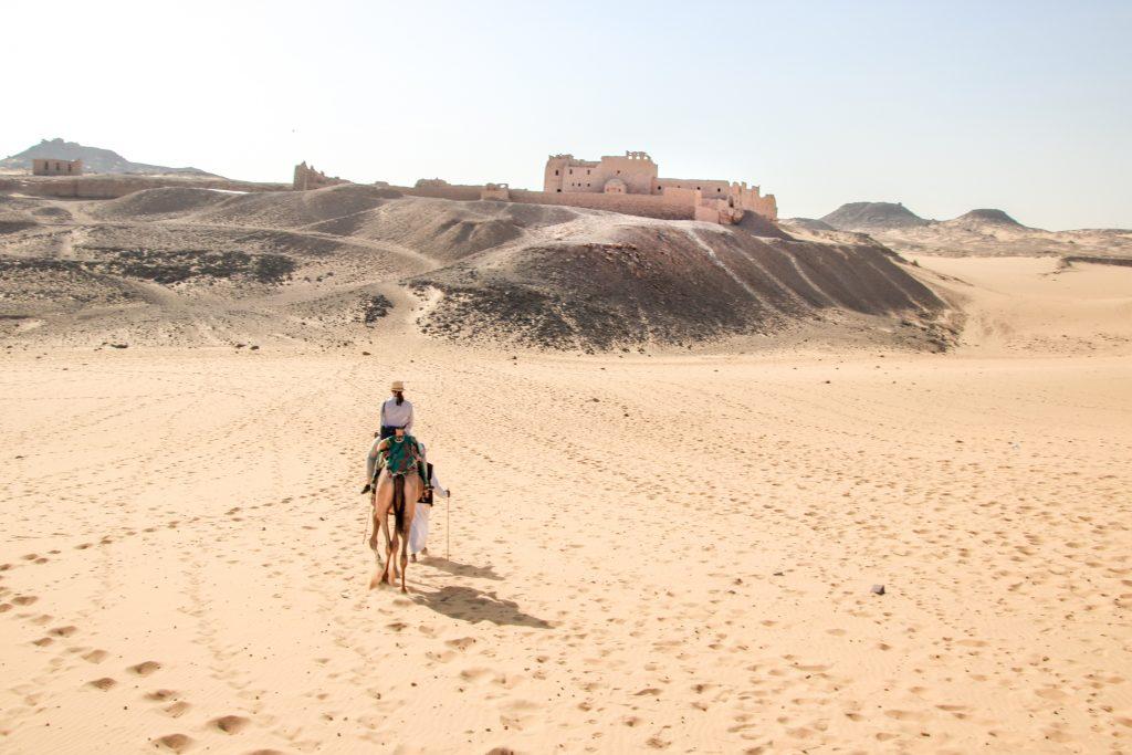 vrouw op kameel in woestijn, Aswan, Egypte