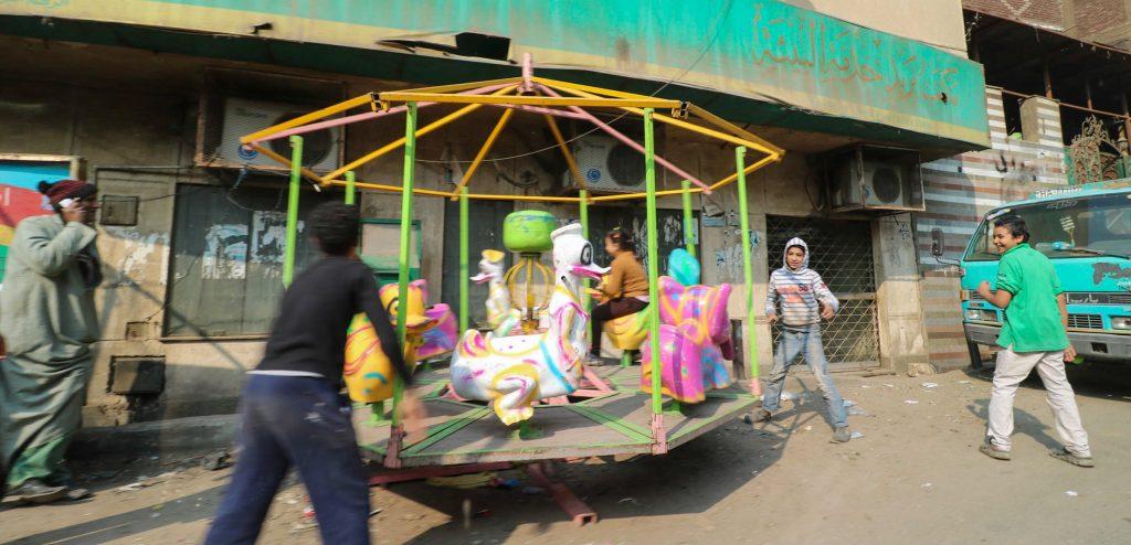 Caroussel met sepelende kinderen, straatbeeld  Manshiyat Naser, Caïro