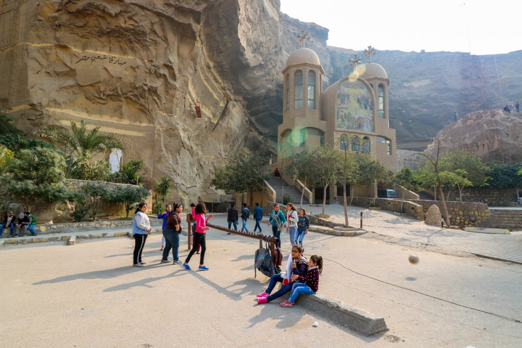 Kinderen spelen bij grotkerk Zabbaleen, afvalstad van Caïro
