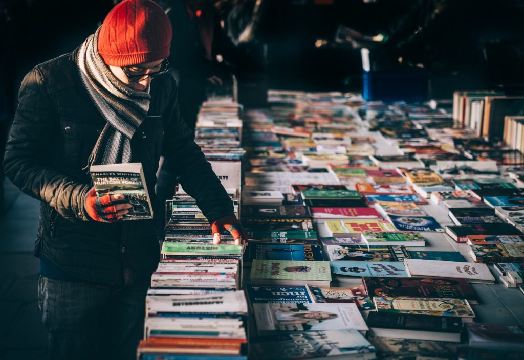 Man in winter clothes searching through books on table of outdoorbook shop
