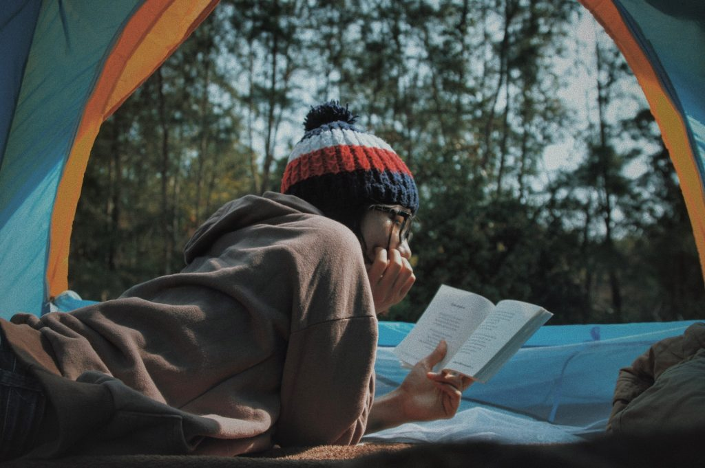 Woman reading a book in a tent in the forest - reading Dave Eggers books as a traveller